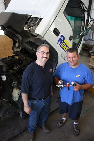 Fuel booster: Jeremy Stanford of Stanford LP Gas Inc and Perry DeSilva of Bermuda Gas with the propane injection system which will be used in all Bermuda Gas trucks